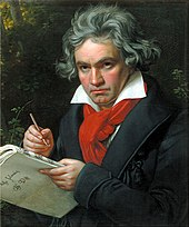 A man with long grey hair holding a pen and music paper