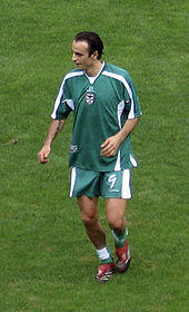 A tall, dark-haired man wearing green shirt, shorts and socks looks to his right as he jogs towards the viewer.
