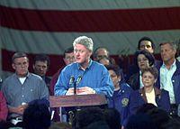 Bill Clinton is standing at a podium speaking to a crowd. The former mayor of Grand Forks is at the right of the image.