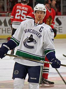 "An ice hockey player wearing a white and blue jersey with a logo of a stylized orca in the shape of a ""C"". He stands relaxed on the ice looking forwards."