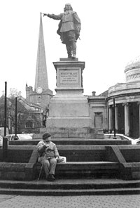 In the foreground is a statue of a man on a plinth above steps, with person sitting on them. In the background is a church tower. The picture is arranged so that the outstretched arm with a pointing finger of the figure appears to be touching the top of the tower.