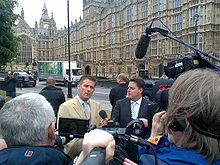A crowd of journalists and photographers are addressed by two men, standing in front of the Palace of Westminster.