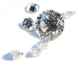 Seven clear faceted gems, six small stones of similar size and a large one.