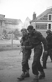 two British soldiers one appears wounded being helped by his comrade with a German guard in the background