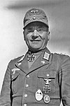 A man wearing a field cap e military uniform with various military decorations including an Iron Cross displayed at the front of his uniform collar.