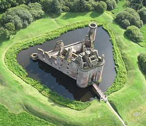 An aerial view of a stone building with a triangular plan. It is