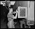 Carpenter on Dog Box door Otahuhu. PHOTOGRAPHER J.F. Le Cren DATE 1953.jpg