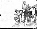 Civilians climbing aboard a vessel with an officer lending a hand, 1890-1953 (7688334486).jpg