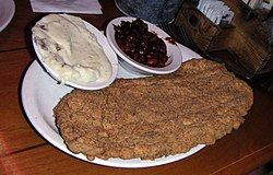 Country-fried steak, with baked beans and mashed potatoes with white gravy