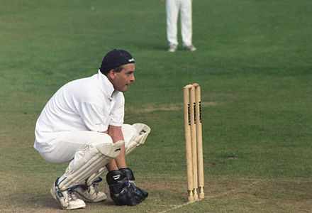 Wicket-keeper in characteristic full squatting position, facing a delivery from a slow pace or spin bowler Cricket wicket keeper.jpg