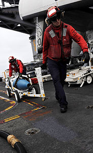 Defense.gov News Photo 110513-N-OY799-122 - Petty Officer 2nd Class Jeffrey Anderson right and Petty Officer 1st Class Michael Washa move ordnance on the flight deck of the aircraft carrier.jpg