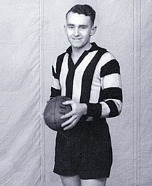 A dark-haired footballer in a long-sleeve black-and-white vertically-striped guernsey and black shorts, holding a football