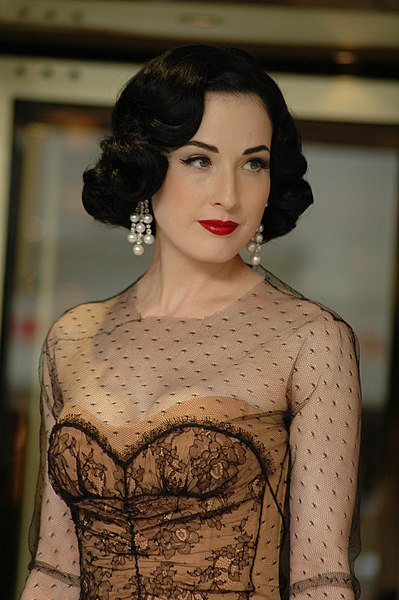 Photo of Dita Von Teese in a 1940s-style sheer top over an elegantly embroidered tan bustier, hair and pearl earrings and makeup all in the same style.