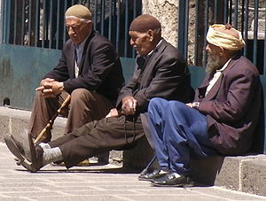 English: Three men in the courtyard of the Gre...