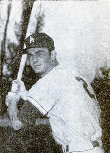 "A man in a white baseball jersey with a block ""2"" on the reverse and dark cap with an interlocked white ""LA"" on the face holds a baseball bat over his right shoulder"