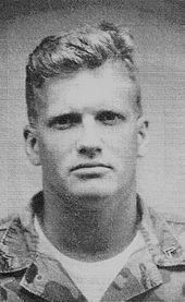 Head shot of a young, blond Carey dressed in military fatigues.