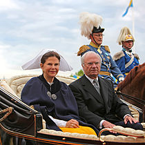 King and queen of Sweden, seated in a pulled cart, with mounted royal guards in background