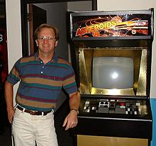 "Ed Logg standing next to a very rare ""Gold Asteroids"" cabinet at Atari."