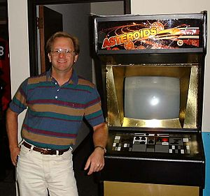 """Ed Logg - Logg in 1999, standing next to a very rare """"Gold Asteroids"""" cabinet at Atari."""