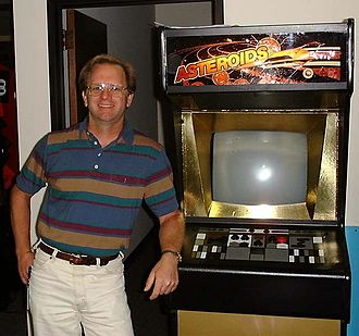 "Ed Logg - Logg in 1999, standing next to a very rare ""Gold Asteroids"" cabinet at Atari"