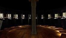 Photographie en couleurs d'une pièce circulaire à l'éclairage tamisé et indirect, des artefacts nichés au sein de vitrines dressées sur le pourtour, un pilier en bois s'élevant au centre de la salle.