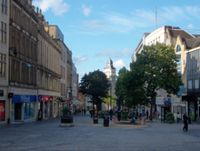 Fargate shopping precinct, Sheffield. Once a busy road, it has been pedestrianised for several decades and is Sheffield's main City Centre shopping area, home to many well known companies. The image shows classical architecture on both sides with one plan spaces in the centre, dotted with trees and the buildings on the High Street are visible beyond the trees.