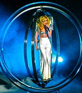 A blond female singing in a microphone in her left hand. She wears white pants and a silvery sparkling top with large shoulder pads. Her golden yellow, blond curls fall on her shoulders. Surrounding her, a number of giant metallic rings are visible. Bluish smoke is visible behind her.