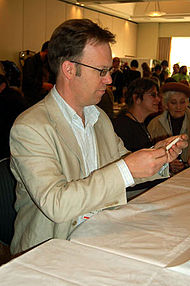 A man facing the right focused on his upper body. He is wearing a light brown jacket, and a white shirt.