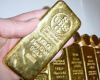 A hand holding a gold bar surrounded by several gold bars and other gold pieces in the background.