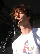 Gotye performing live with his microphone, while closing his eyes.