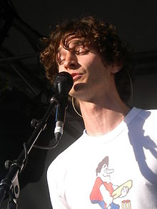 A Caucasian man with curly hair sings into a microphone.