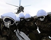 Colour photograph of five fully covered marines in a huddle underneath a helicopter.