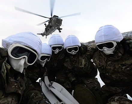 Ground crew with the Commando Helicopter Force huddle from the downwash of a Sea King helicopter on exercise in Norway. Groundcrew Sheltering from Helicopter Downwash in Norway MOD 45155036.jpg