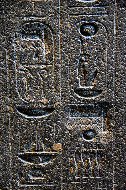 Hieroglyphs on the backpillar of Amenhotep III's statue. There are 2 places where Akhenaten's agents erased the name Amun, later restored on a deeper surface. The British Museum, London Hieroglyphs on the backpillar of Amenhotep III's statue. There are 2 places where Akhenaten's agents erased the name Amun, later restored on a deeper surface. The British Museum, London.jpg