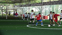 Men playing football on artificial grass pitch.