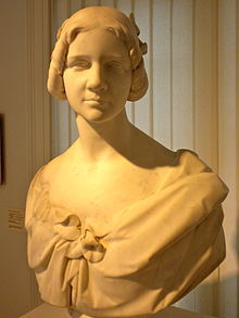 Photograph of a stone bust of a young woman looking directly at the reader. The stone appears to be white marble. Her hair is cut well above her shoulders. She is wearing a dress that hangs loosely from her shoulders, leaving her neck and upper chest bare.