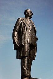 Bronzestatue von Diefenbaker, von einer Seite genommen.  Er trägt einen Mantel über einem Anzug.  Er trägt die Bill of Rights unter dem Arm.
