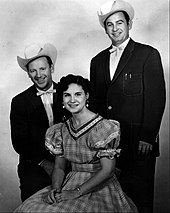 Two men wearing dark suits and cowboy hats standing either side of a woman wearing a gingham dress