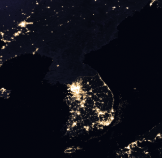 Satellite image of the Korean peninsula taken at night showing the extent of the division between the Koreas; note the difference in light emitted between the two countries Korea at night.png