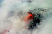 Photo showing clouds of steam surrounding lava that is partly black and partly glowing orange.