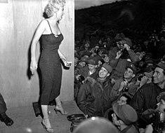 Monroe stoi na podium w obcisłej sukience i sandałach na wysokim obcasie, witając się z tłumem amerykańskiej piechoty morskiej