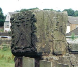 Maybole - The head of the old Maybole Cross in the gardens of Maybole Castle. The cross bears the coats of arms of the Kennedy family of Cassillis and has a rare Moon dial on one face.