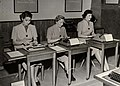 Modellerna visar passande klädesplagg för kontoristen, februari 1952. Tre kvinnor skriver på maskin - Nordiska museet - NMA.0043609.jpg