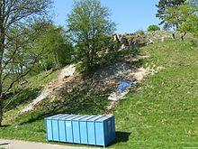 Photographie en couleurs d'un terrain en pente creusé parsemé de gravats, un conteneur bleu turquoise visible au premier plan.