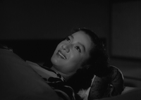 Noriko, in traditional costume, lying on a futon and covered with a blanket, stares at the ceiling, smiling