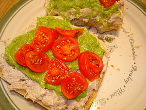 Tuna fish sandwich - An open tuna fish sandwich with guacamole and cherry tomatoes