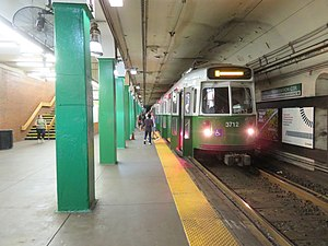 A green light rail train at an underground station