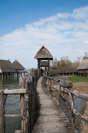 History of construction - A reconstruction of a neolithic fortified village showing a palisade wall and stilt houses at the Pfahlbau Museum Unteruhldingen, Germany.