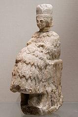 Statuette d'orante assise coiffée du polos et tenant un rameau dans la main gauche