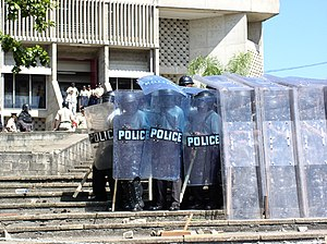 Shield wall - Police form a testudo shield wall.